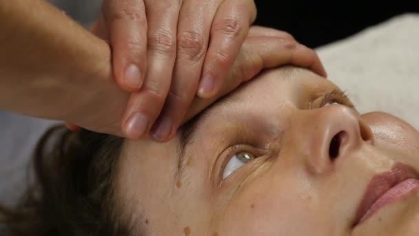 műanyag arc masszázs spa saton. nő élvez a szolgáltatások egy profi masszázs terapeuta. lassú mozgás