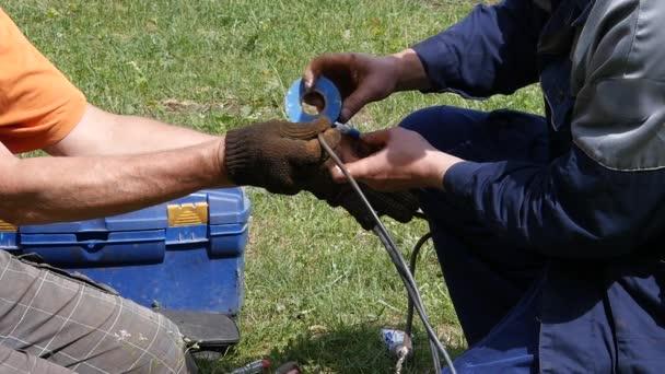 připojení vodičů a izolace, venkovní práce. elektrikář rukou, nástrojů a dráty. pomalé motoin