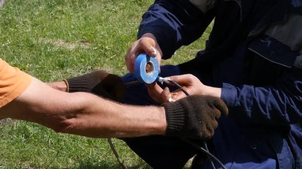 Closeup elektrikář rukou, nástrojů a dráty. Izolace elektrických kabelů. Zpomalený pohyb