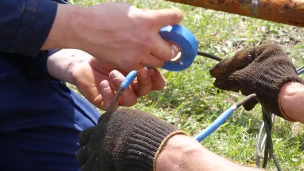 Closeup elektrikář rukou, nástrojů a dráty. Izolace elektrických kabelů. 4k