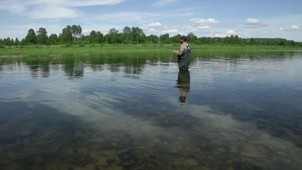 Radostné rybář loví v klidné říční vody u pobřeží