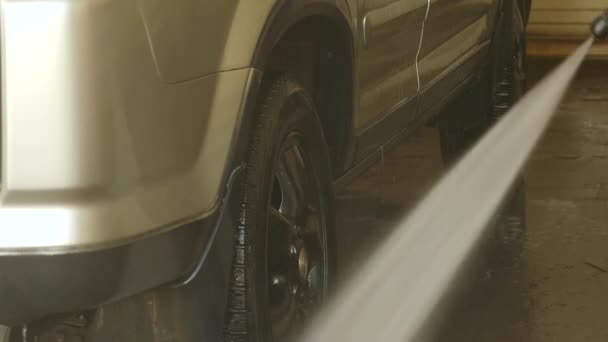 Muž, mytí auta v mytí aut služby. Auto vyčistit s vodním paprskem umýt. Zpomalený pohyb