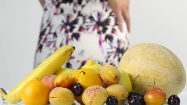 Slim young woman choosing fruits. Healthy eating. Weight loss and dieting concept. 4K