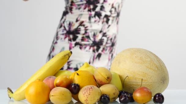 Štíhlá mladá žena výběr ovoce. Zdravé stravování. Hubnutí a diety koncept počtu zavazadel. Zpomalený pohyb