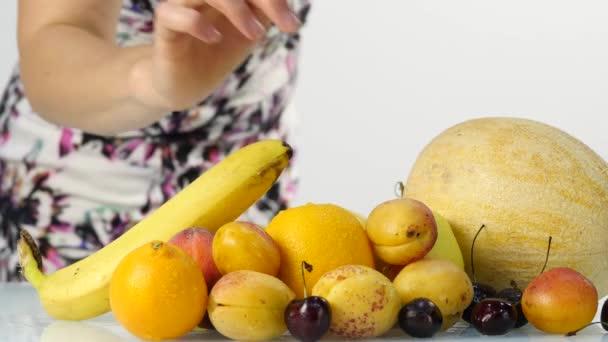 Štíhlá mladá žena výběr ovoce. Zdravé stravování. Hubnutí a diety koncept počtu zavazadel. 4k