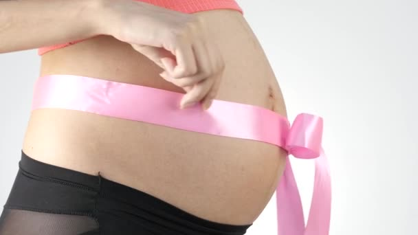 Těhotná žena s růžovou stuhou na břiše. 4k