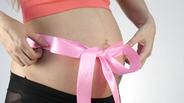 Těhotná žena s růžovou stuhou na břiše. Zpomalený pohyb