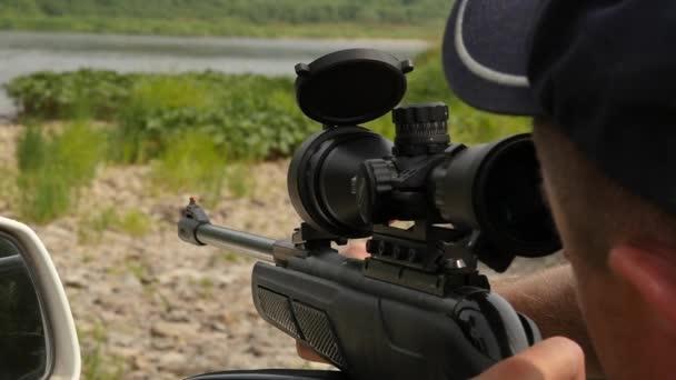 Muž střelbě vzduchovku zbraň s optickým zaměřovačem během dovolené na divoké přírody. Zpomalený pohyb