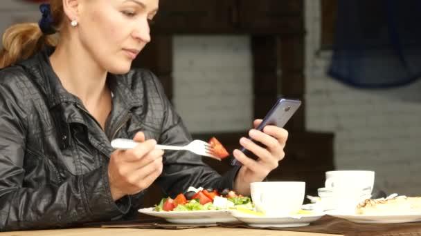 podnikatelka, jíst salát ve venkovní kavárně. dívka jíst zelené chutné jídlo a kontroly e-mailu v telefonu. 4k