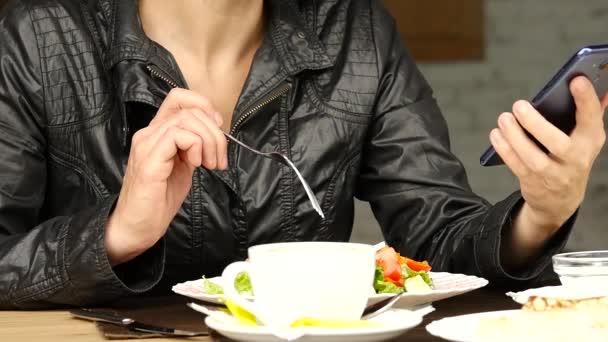podnikatelka, jíst salát ve venkovní kavárně. dívka jíst zelené chutné jídlo a kontroly e-mailu v telefonu. Zpomalený pohyb