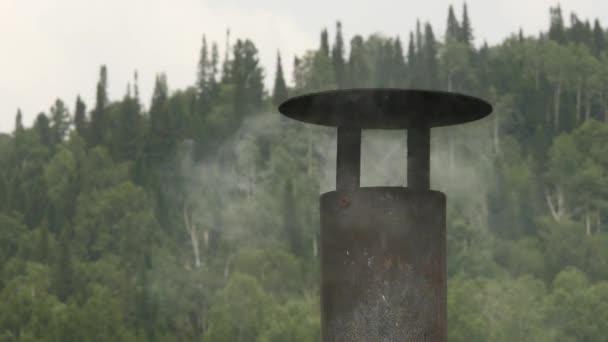Kouř vychází z železné komína domu. Kouří komíny na pozadí stromů. 4k