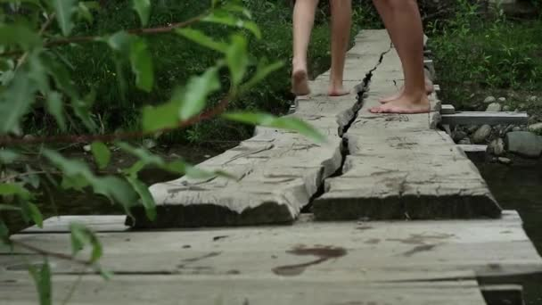 teenagers legs walking along a narrow wooden bridge over a mountain river. camping and adventure concept