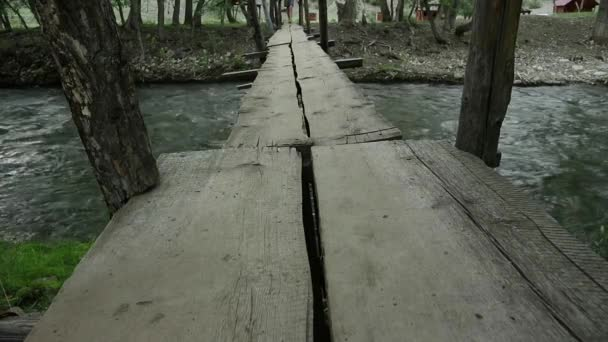 womans legs are walking along a narrow wooden bridge over a mountain river. camping and adventure concept