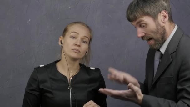 Angry boss scolding young employee for bad result. indifferent girl listening to music on headphones. 4K