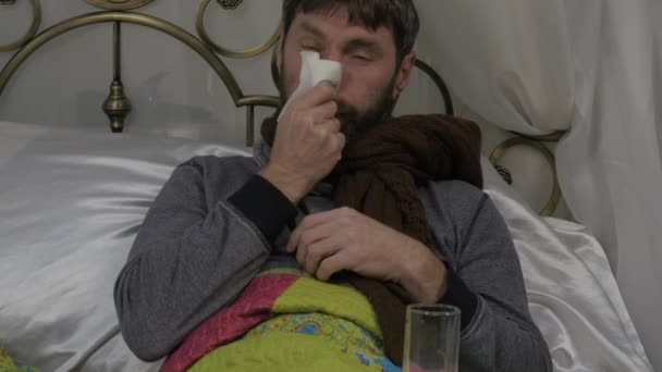 Ein kranker Mann liegt im Bett mit einen warmen Schal um den Hals, seine Nase wie eine laufende Nase bei einer Erkältung oder Grippe. 4k