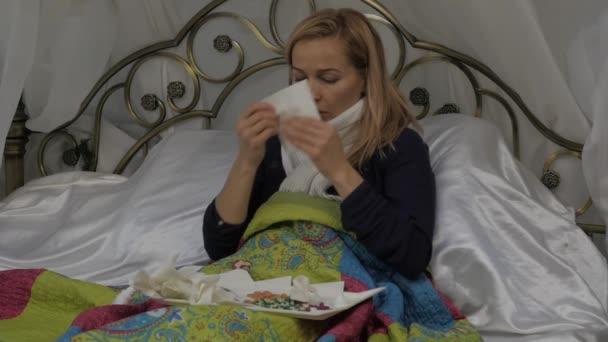 Eine kranke Frau liegt in einem Bett mit einem warmen Schal um den Hals und bläst seine Nase wie mit einer laufenden Nase während einer Erkältung oder Grippe