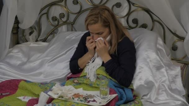 Nemocná žena leží v posteli, vysmrkal jako rýma během nachlazení nebo chřipky. Zpomalený pohyb