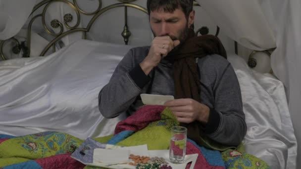 Ein Kranker liegt mit einem warmen Schal um den Hals in einem Bett, hustet und trinkt Tabletten. Zeitlupe