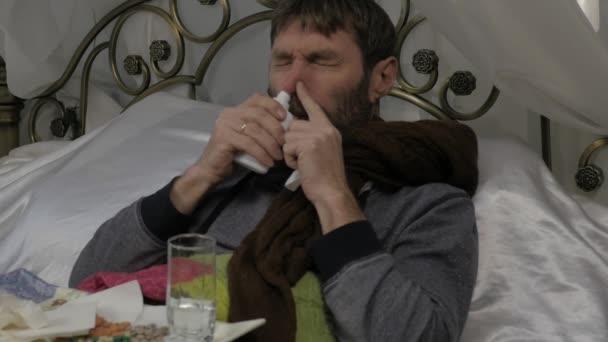 Ein kranker Mann liegt im Bett mit einen warmen Schal um den Hals, ein Medikament in die Nase spritzt. Nasenspray. Slow-motion