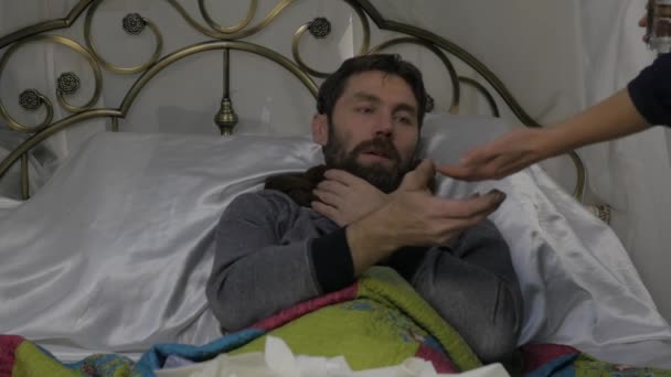 Traurig kranker Mann mit einen warmen Schal um den Hals, bringt Frau Pillen und ein Thermometer. Slow-motion