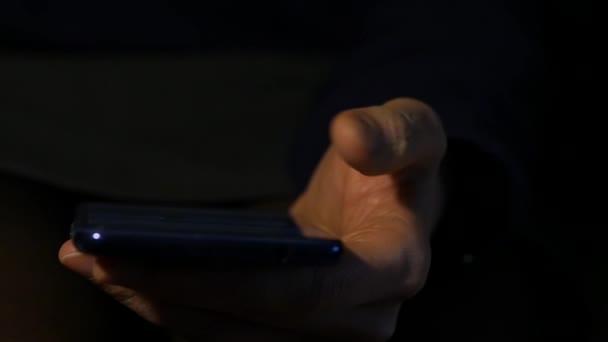 zblízka Dámské prsty používáte smartphone v noci. dívka, prohlížení internetu na mobilním telefonu. Zpomalený pohyb