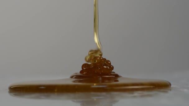 Detail medu kape. Lití med na povrchu. Zpomalený pohyb.