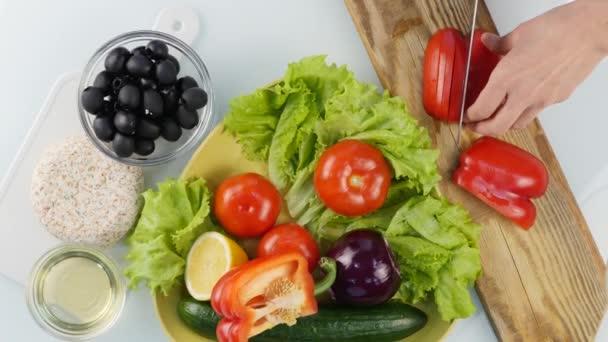 Ansicht von oben. Frauenhände schneiden süße rote Paprika auf einem Küchentisch. Gemüse auf einem Holzschneidebrett schneiden. 4k