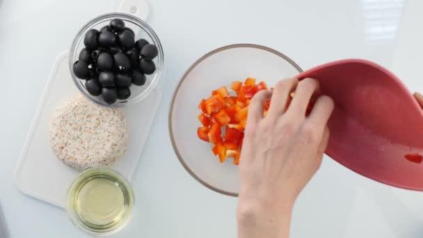 Pohled shora. žena vaření Vegetariánská nízkokalorické Řecký salát, klade zeleninu do mísy. 4k