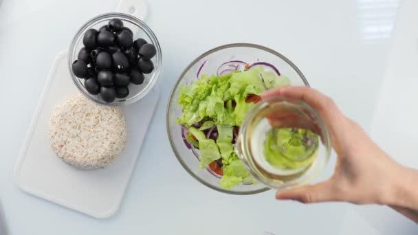 Pohled shora. žena vaření Vegetariánská nízkokalorické Řecký salát, zalévání zeleniny s olejem. 4k