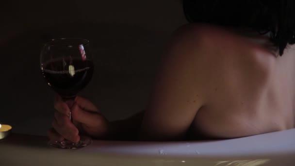 Zadní pohled na krásné mladé ženy, relaxaci v lázni a pití červeného vína