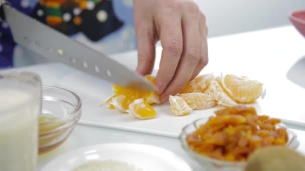žena řez mandarinka ovocný salát na prkně. zdravé vaření. 4k