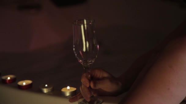 Zadní pohled na krásné mladé ženy, relaxaci v lázni a pít šampaňské