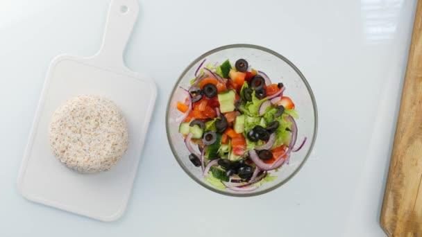 Top view. woman cooking vegetarian low calorie Greek salad, puts vegetables in a bowl. 4K