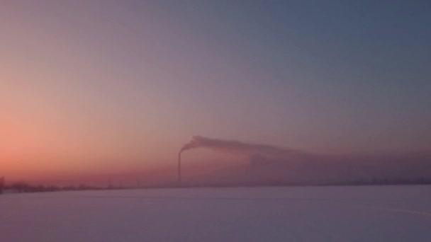 Létání nad sněhová pole a západu slunce a osamělý komín stonek s kouř na obzoru