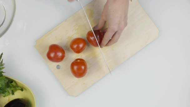 ženy používající kuchyňský nůž snímku řezané čerstvé rajče na dřevěném prkénku. Krájení rajčatový salát nebo pizzu. Pohled shora 4k