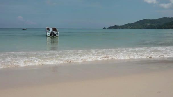 Seelandschaft mit Wellen am Sandstrand mit großen Boot. bewölkten Himmel und tropischen Strand