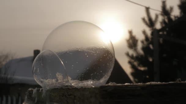 gelido della bolla di sapone. Globo di neve ghiacciata. Reticoli del ghiaccio del fiocco di neve ghiacciato sulla palla di sapone. Priorità bassa di tramonto di inverno