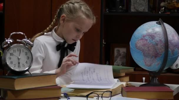 Školák dělá domácí úkoly, malá blondýnka u stolu. dětské vzdělání. 4k