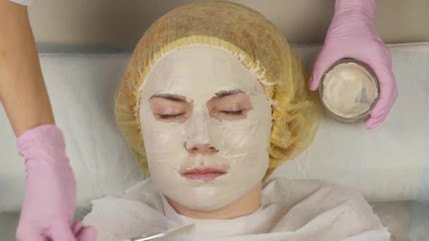 Kosmetologe, der Gesichtsmaske auf Problemhaut aufträgt. junge Frau bei der Reinigung der Haut. 4k