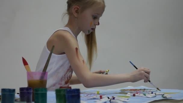 Kis iskolás. Aranyos kislány festő támaszkodik az asztalra, és a maga ruháit. lassított mozgás