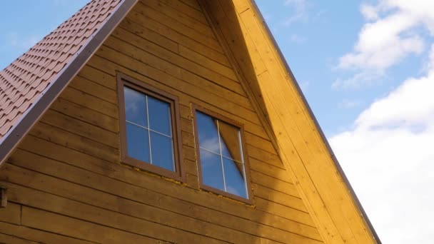 wooden house, glass window with reflection of clouds, fast moving clouds. timelaps