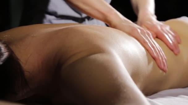 masáž zad v lázeňském salonu. Masážní terapeut na ženské tělo dělá klasickou masáž
