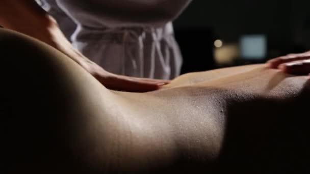 masáž na zádech v lázeňském salonu. Masážní terapeut na ženské tělo dělá klasickou masáž