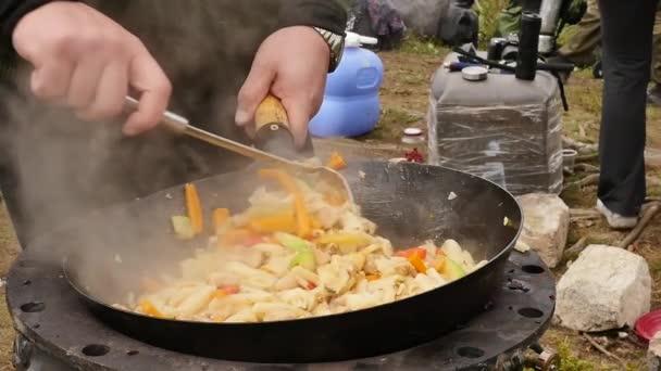 főzés zöldségek hússal a szabadban. sült zöldségek egy bográcsban. vakáció Concepte. a füst lassan emelkedik a serpenyőbe. lassított mozgás.