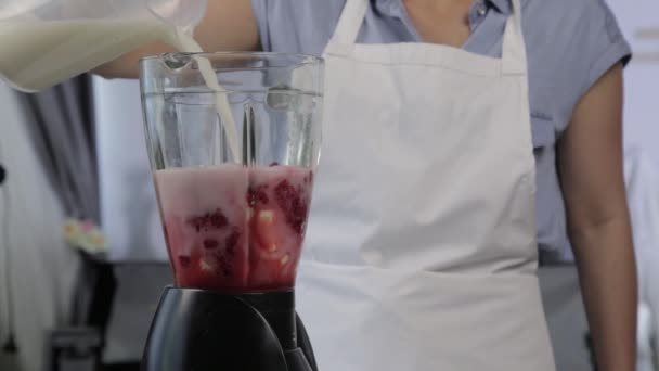 young woman cooking a fruit and berry cocktail in a blender. Pouring milk in blender with raspberries. healthy eating and dieting concept