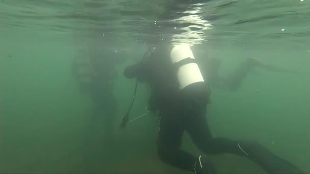 Taucher erkunden einen Bergsee. Zeitlupe. Schlechtwettertauchen, Eiswasser