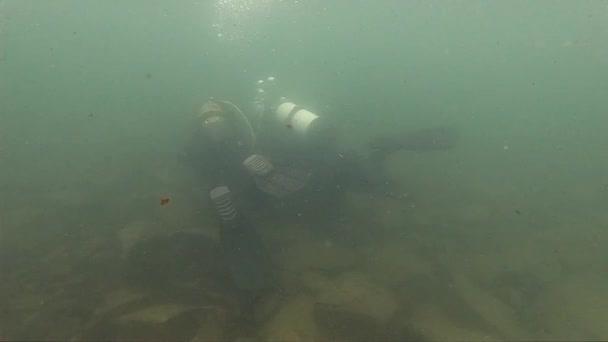 Tauchlehrer, der einen Tauchkurs im Flachwasser leitet. Erforschung eines Bergsees im Eiswasser