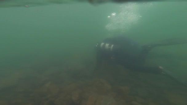 Taucher erkunden den felsigen Boden im flachen Wasser. Ausbildung junger Taucher. Zeitlupe. Abtauchen in einen Bergsee