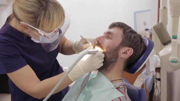 female dentist is treating a patient in dental clinic. Dental check up. Stomatologist treats caries in patients teeth