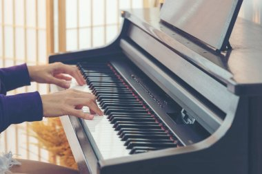 Close up hand playing the piano. Teen Woman relaxing and playing the piano in the livingroom. Yong player musical for lifestyle concept.